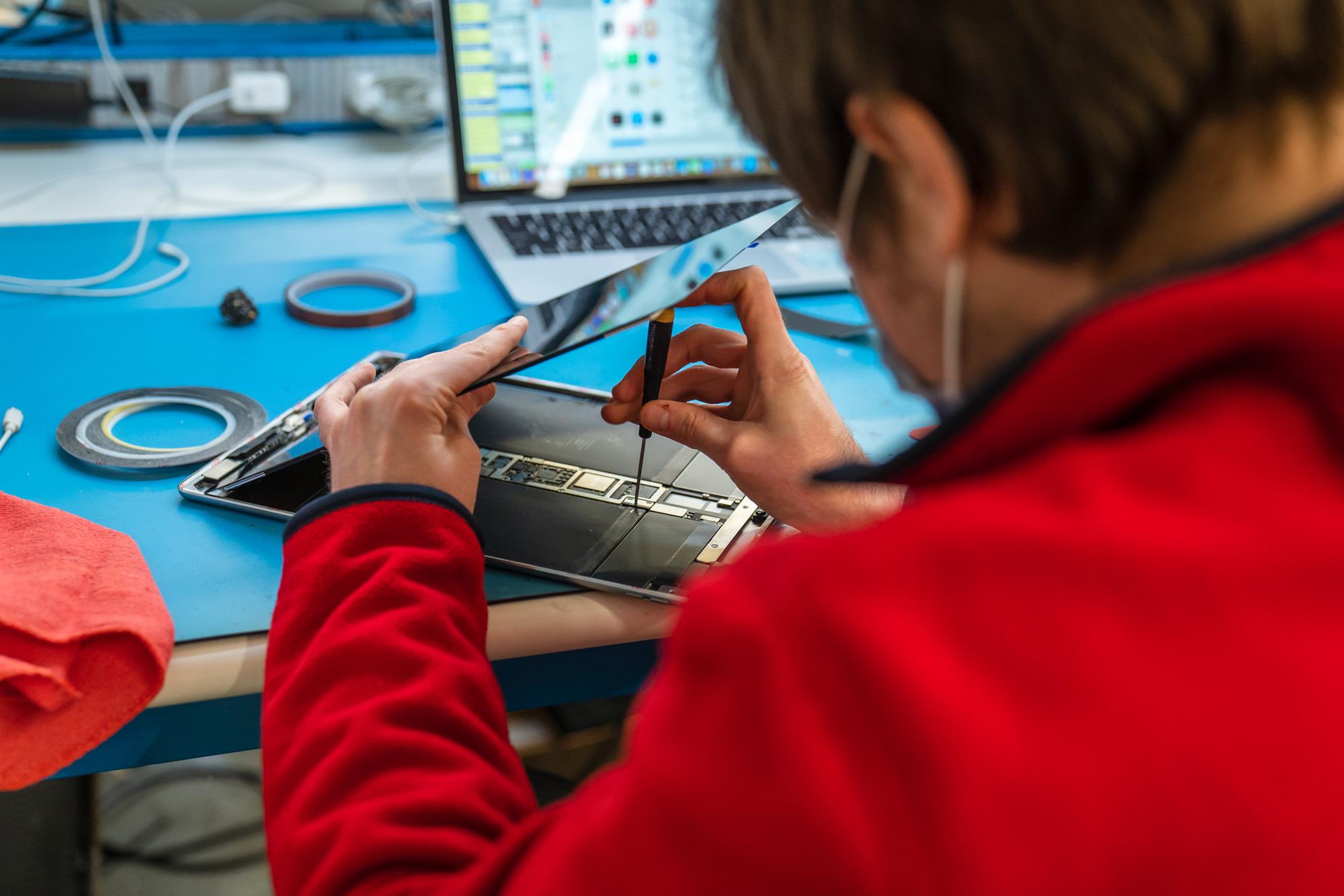 iResQ employee repairing a tablet
